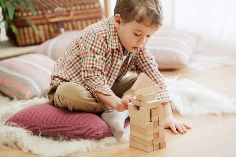 Un enfant joue avec un jeu de construction en bois